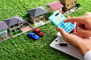 Man with calculator above model houses