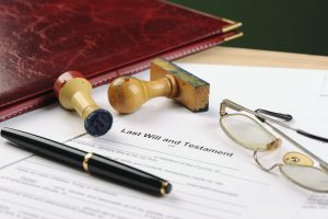 Reading glasses, pen, stamp, wax seal on top of Last Will and Testament