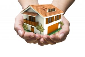 Hands cupped together holding double storey house