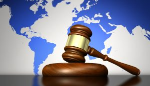 Court gavel and block in front of world map