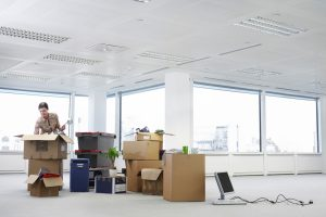 Woman unpacking boxes in empty commercial office space