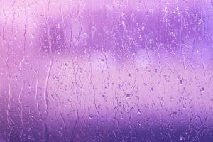 Rain against window with purple background