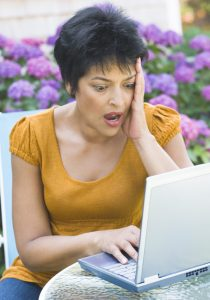 Woman looking surprised at laptop