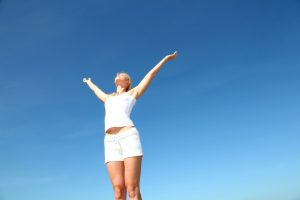Woman with arms spread apart in front of vivid blue sky