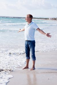 Man standing at waters edge at beach with arms spread